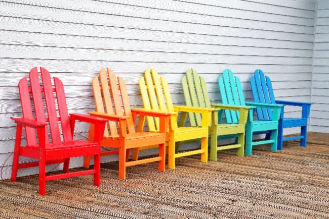 A multi-color grouping of painted chairs -- six Adirondack chairs against a clapboard siding wall with each one painted a different color (red, orange, yellow, pale green, aqua, and blue).