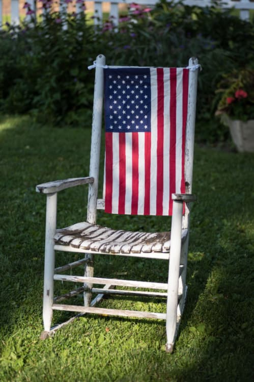 An antique rocking chair with white distressed paint and an American flag on the back of the chair -- a patriotic painted chair theme.