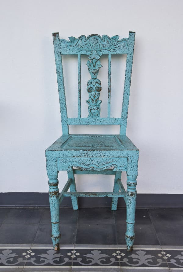 A wooden chair with carved ornate detailing and distressed blue paint -- an example of a shabby chic painted chair.