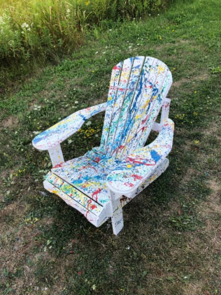 A white painted Adirondack chair with splattered paint in primary colors.