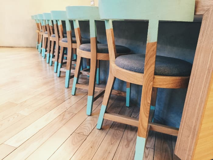 A row of painted chairs at a long bar/counter that have blue paint on the backs of the chairs and also at the bottoms of the legs -- all other parts of the chair are stained wood.