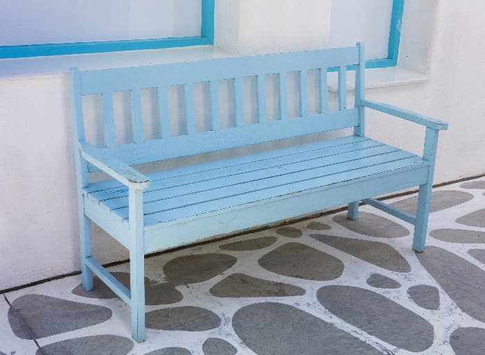 A blue painted bench on a patio next to an exterior wall.  While chalk paint is best for indoor projects, it can be used for outdoor items if the paint coat is properly sealed to provide protection from the elements.