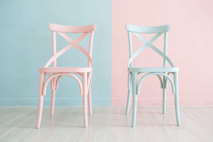 A pair of painted chairs, one painted pale pink against a pale blue background, the other painted pale blue against a pale pink background.