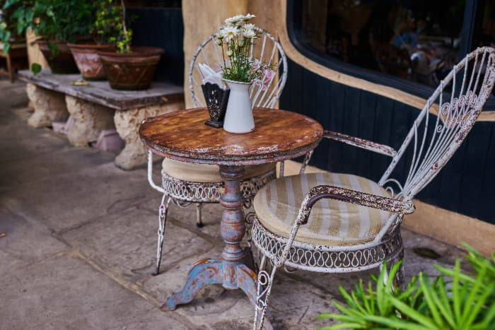 Outdoor patio/porch scene with a round painted table that has been distressed and given a patina to make it appear aged.  Two distressed painted metal chairs with striped cushions are on either side of table.