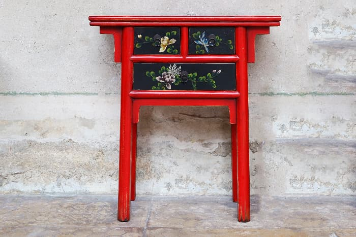 A Chinese-style painted table with a red lacquered paint job.