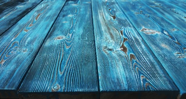 Closeup of a plank table painted with a blue color wash -- another method for how to distress furniture with chalk paint.