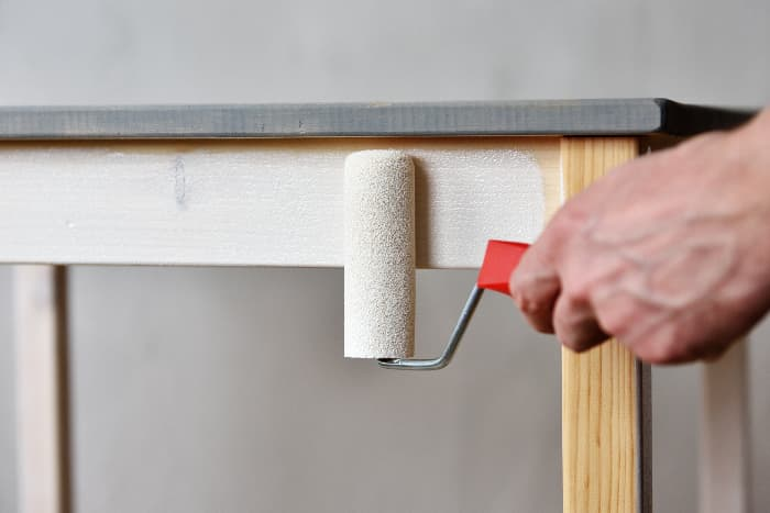 Closeup of a man's hand painting the base of a table white with a small paint roller.