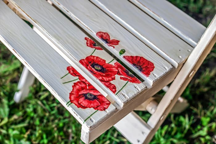 Closeup of a white painted chair seat that has poppies painted in one corner as a decorative detail.