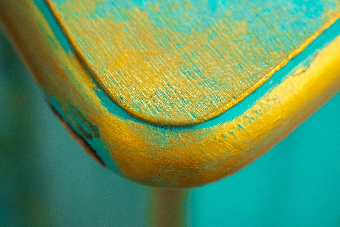 A closeup of a corner of a table with layers and yellow and blue paint that create an aged look -- paint layering is just one method for how to distress furniture with chalk paint.