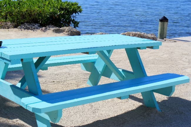 A picnic table painted a light turquoise color -- a fun and festive painted table idea.