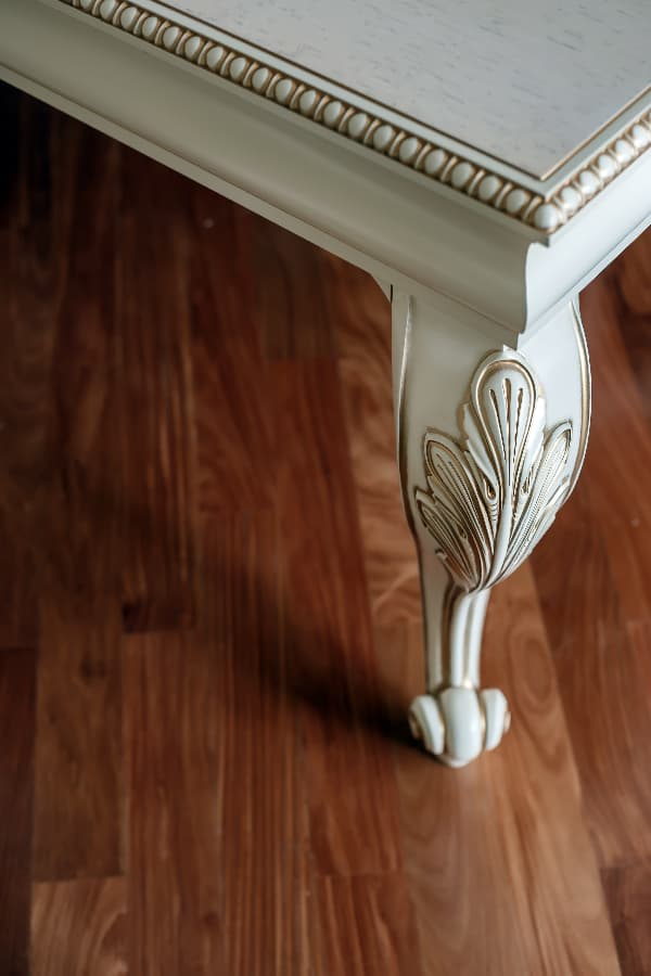Closeup of a painted table leg that has carved details that has carved details with gold paint to create subtle highlight for the piece.