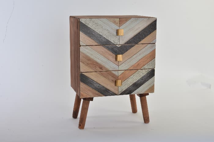 A small cupboard that has been painted to look like wood inlay in a chevron pattern -- an idea for a painted table project.