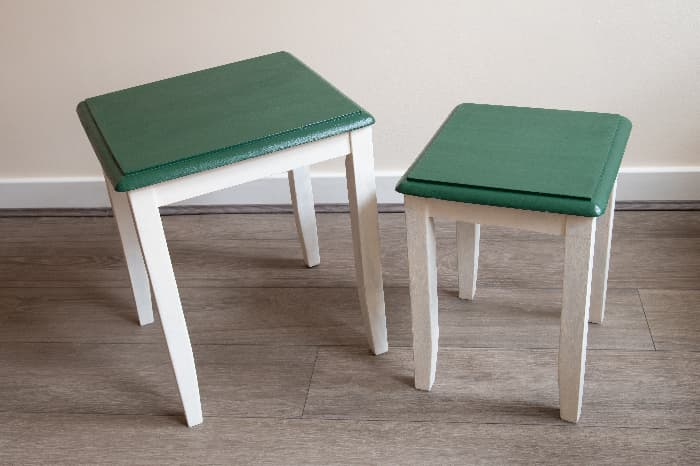 Two small end tables with the tops painted green and the table base and legs painted white -- a simple painted table design.
