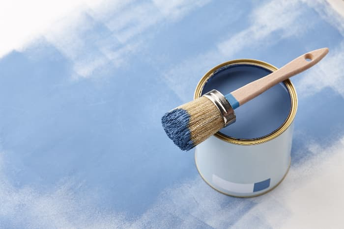 Blue chalk paint being painted over white paint -- an example of when applying a new coat of paint makes it unnecessary to remove chalk paint.