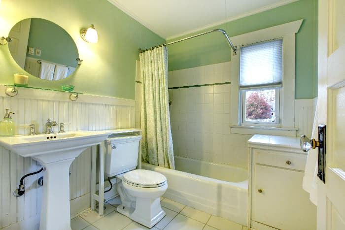 Bathroom with pale green wall color. shower curtain with a white and pale green design, white wainscotting, and woodwork white shower and floor tile, white bathroom fixtures, and a white cabinet.