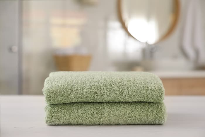 Two stacked towels in pale green color with out of focus modern style bathroom in the background.