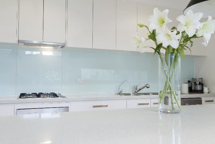 Kitchen with pale green walls, white cabinets, white counters, and stainless appliances with vase of white lilies in foreground.