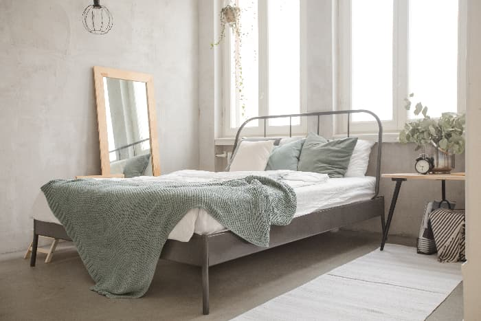 A pale green throw blanket n a modern bed with a gray metal frame located beneath tall, uncovered windows in a white bedroom.