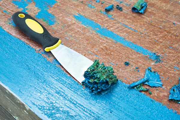 Closeup of scraper removing bright blue paint from a wooden surface -- a demonstration of one method to remove chalk paint.