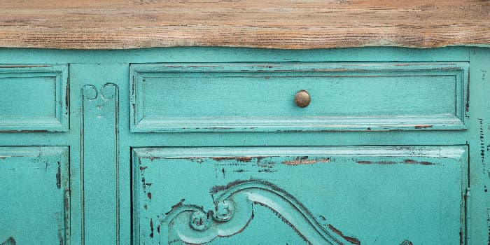 Closeup of a blue dresser or cupboard with a distressed paint job.