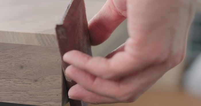 Hand sanding a wooden drawer can help make wood drawers slide easier.