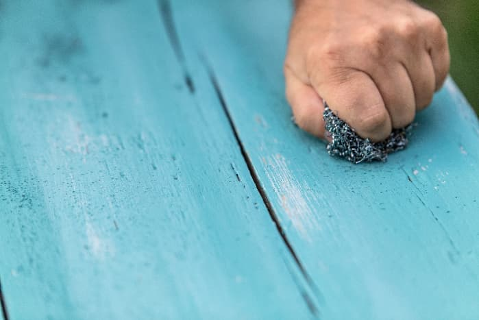 Closeup of man using the sanding technique to remove chalk paint.