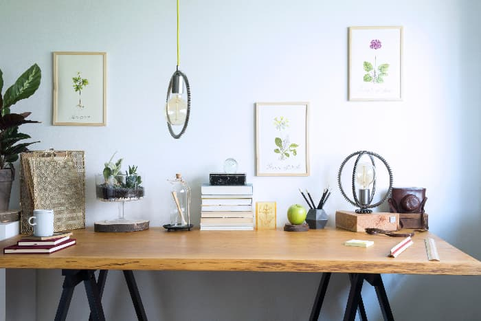 Farmhouse desk made of solid wood piece on black sawhorses against blue wall.