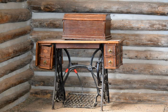 Desk made from antique sewing machine table against log cabin wall.