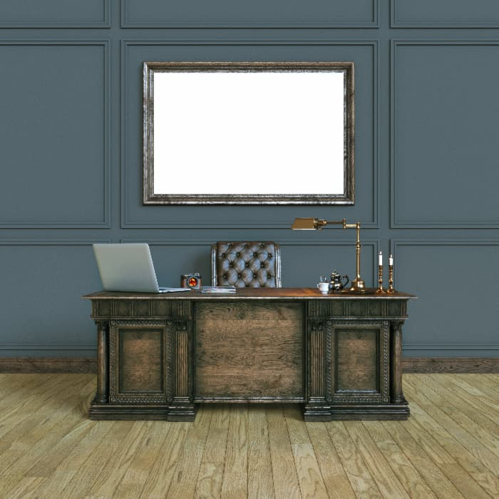 Dark Solid Wood Desk against dark blue wall.