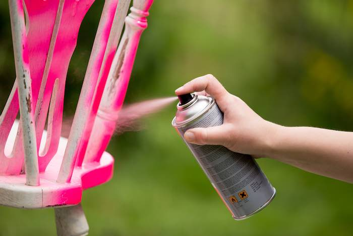 Spray painting an old chair in the color pink, while avoiding blotchy spray paint.
