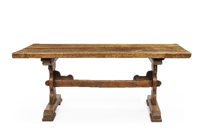Medium wood-stain trestle table serving as a farmhouse desk.