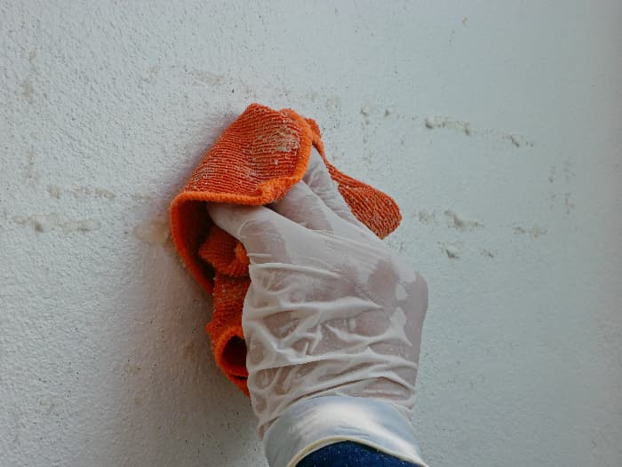Closeup of vinyl-gloved hand wiping a white painted wall with an orange cloth dipped in solvent -- an example of using solvents to remove chalk paint.