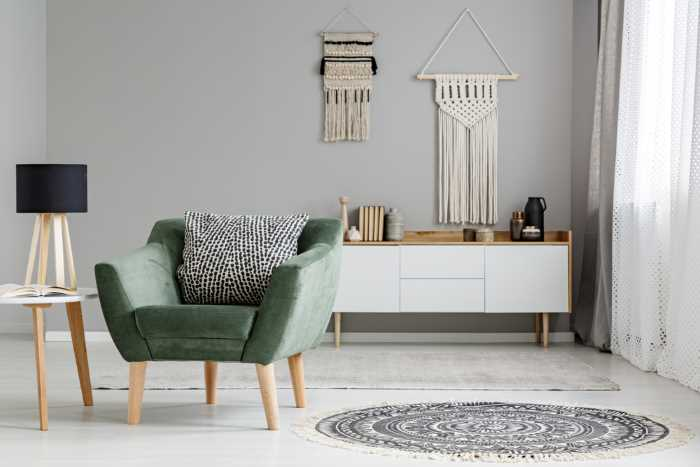 A modern living room with a green upholstered chair and white furniture against light gray walls.