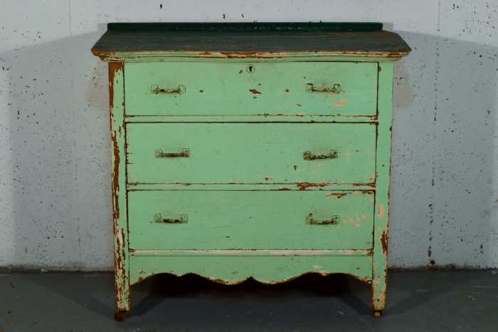 A dresser with a distressed green paint job against a pale lavender wall.