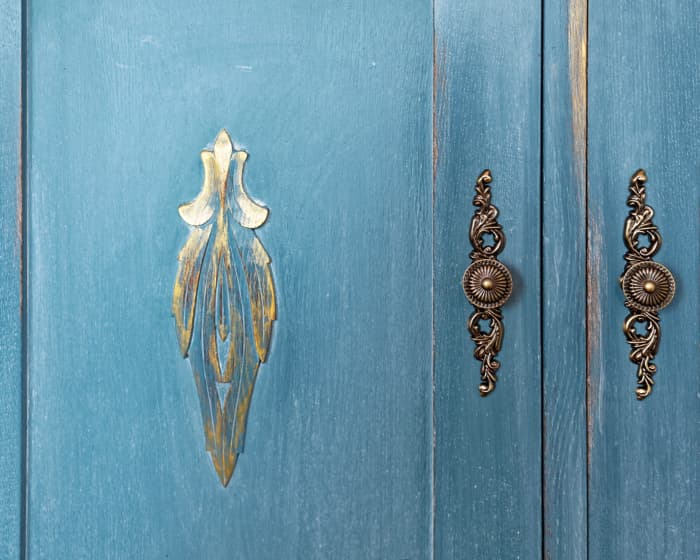 Closeup of cabinet doors painted in a rustic or farmhouse style.
