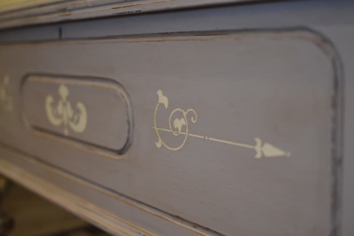 Closeup of a cedar chest painted with gray chalk paint and stenciled with a design