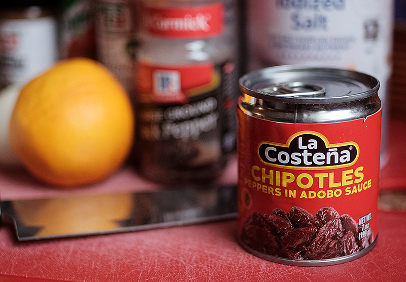 Can of La Costena chipotles with spices and a lemon in the background.