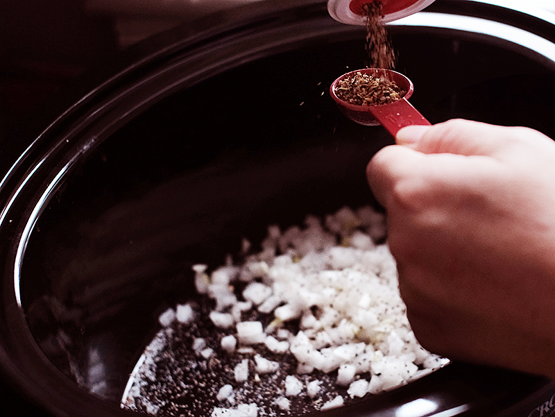Hands pouring steakhouse seasoning mix into a measuring spoon over diced onions in a slow cooker.