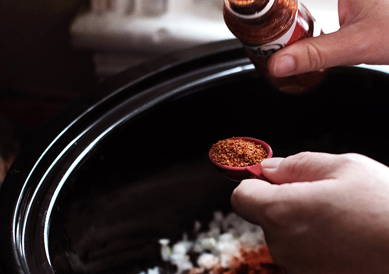Hands measuring out Tajin spice mix over a slow cooker.