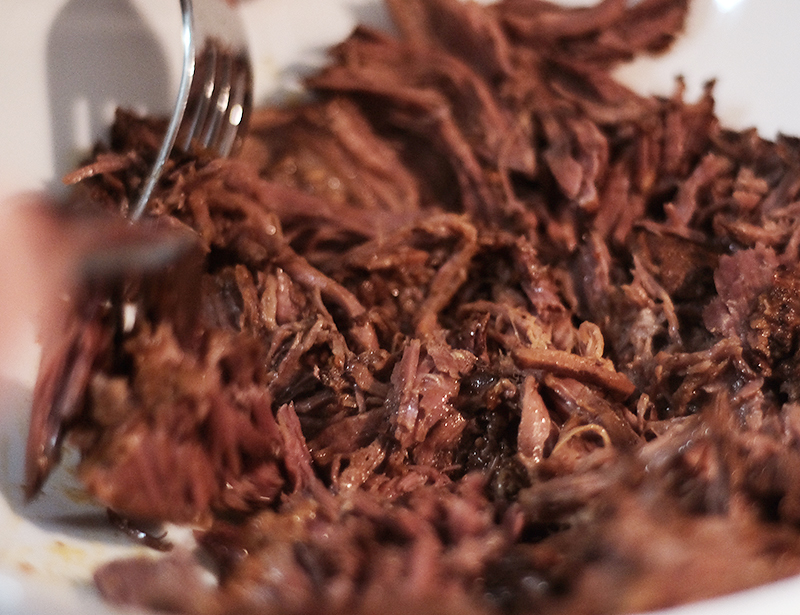 Closeup of shredded meat and a fork.