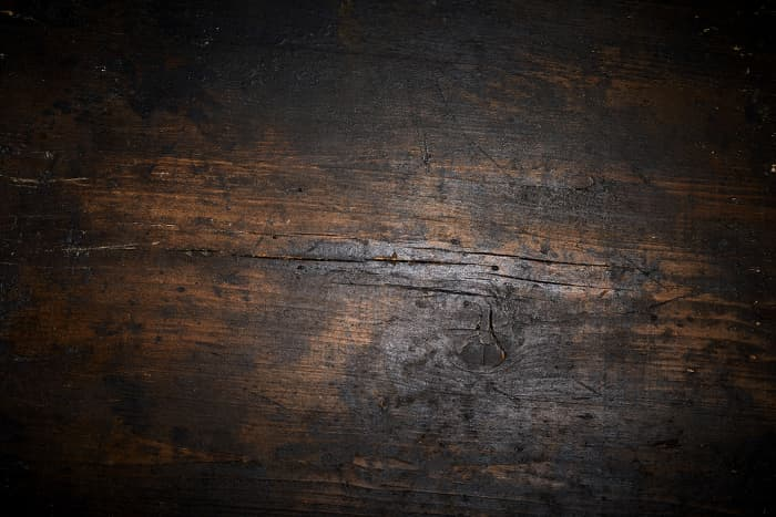 Closeup of wood that appears to be quite old, with cracks, wormholes, gouges, nicks, and dark spots.