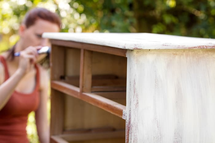 Woman painting a dresser with white chalk paint.