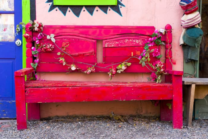 A fuschia colored outdoor bench next to a pink stucco wall.