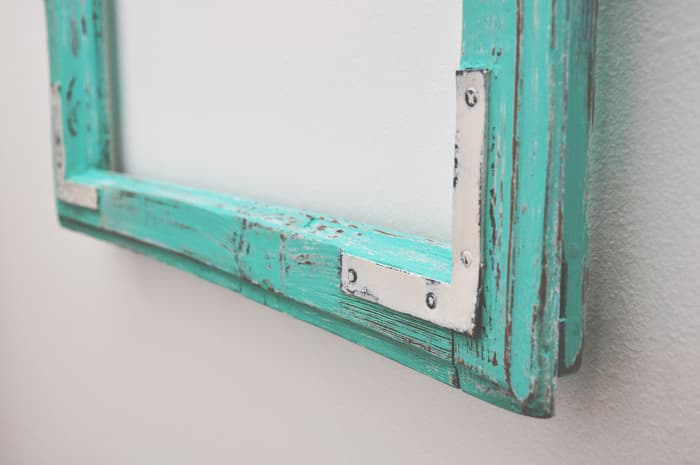 Closeup of bottom edge of painted picture or cabinet frame with distressing.  When you know how to chalk paint furniture, you can apply that knowledge other paint projects.