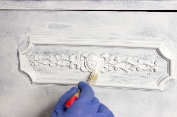 Closeup of hand painting decorative detailing on a piece of furniture. Knowing how to chalk paint furniture may be just what you need to salvage a piece, instead of throwing it away.