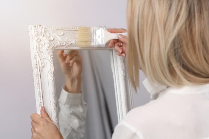 Back view of a woman painting a mirror frame.  Until you get the hang of chalk paints, you might want to paint smaller, non-furniture items at first.